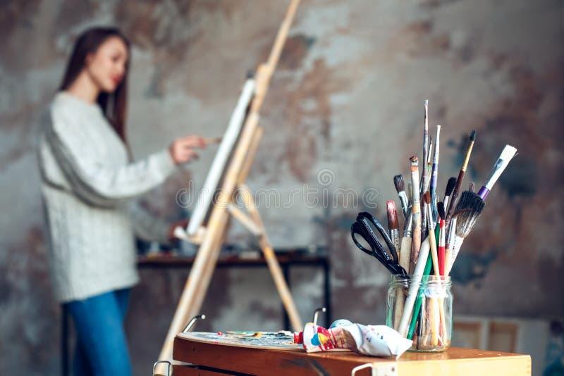 Artista da jovem mulher que pinta em casa o close-up criativo das ferramentas fotos de stock royalty free