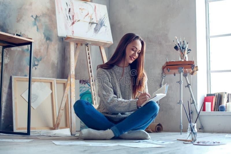 Artista da jovem mulher que pinta em casa o planeamento criativo imagem de stock