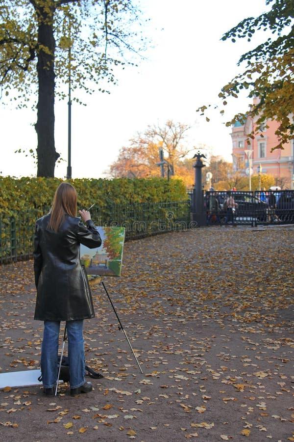 Artista da menina que pinta uma paisagem do outono foto de stock
