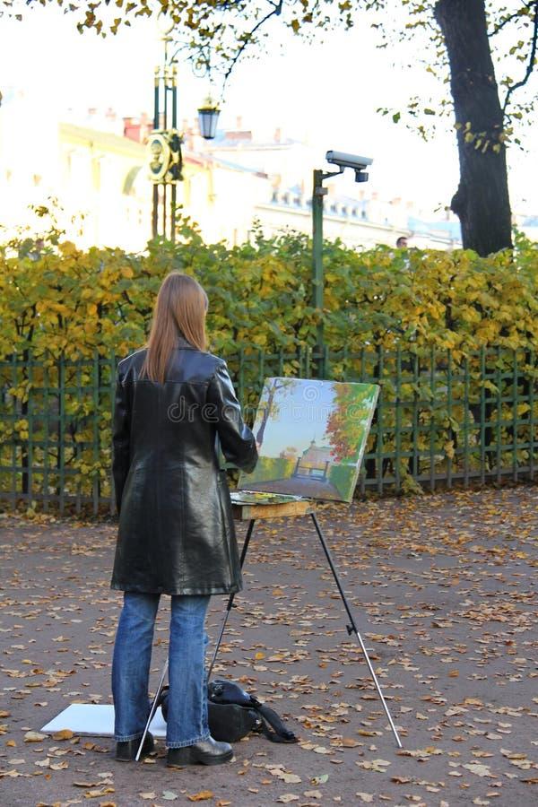 Artista da menina que pinta uma paisagem do outono fotos de stock