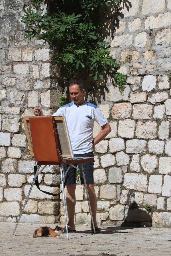 Artista da rua com uma armação e um gato fotografia de stock