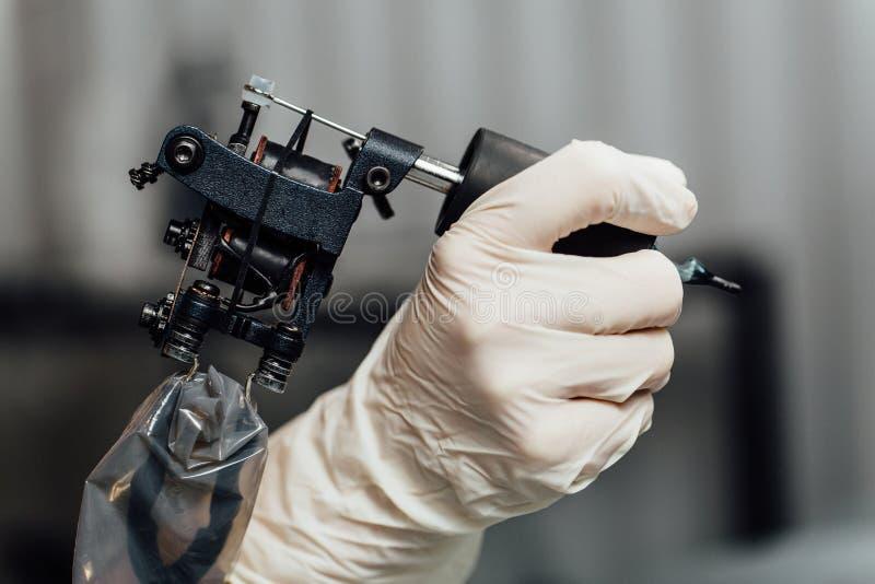 Artista da tatuagem do close-up que guarda a máquina da tatuagem no fundo escuro, máquina para um conceito da tatuagem imagens de stock royalty free