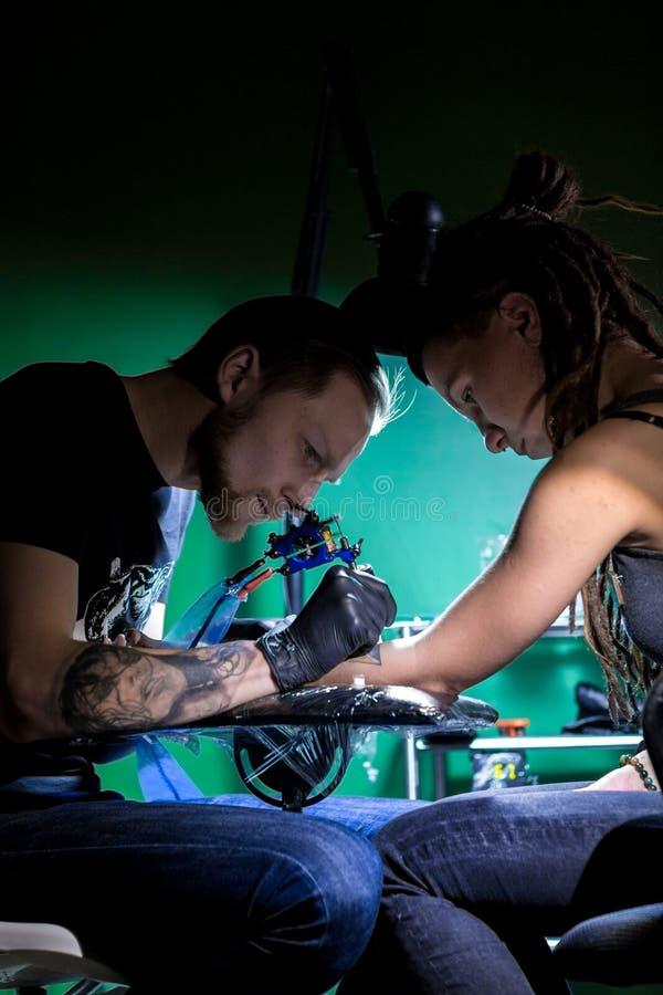 Artista da tatuagem que fazem a tatuagem O mestre trabalha na máquina profissional e em luvas pretas estéreis imagens de stock royalty free