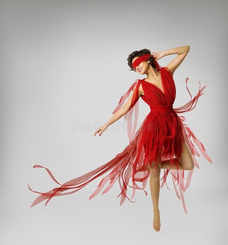 Artista Dancing en vestido rojo, muchacha de la mujer con la banda en ojos imagen de archivo
