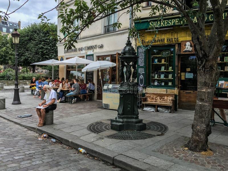 Artista de bosquejo delante de Shakespeare y Company, París; comensales del café en fondo imágenes de archivo libres de regalías