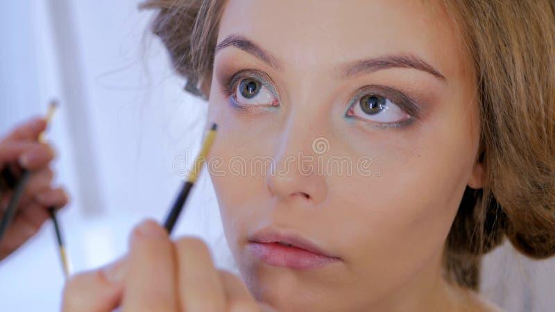 Artista de composição profissional que aplica o lápis de olho em torno do olho inteiro do modelo imagens de stock royalty free