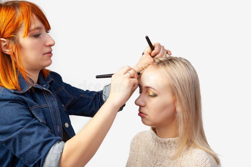 Artista de composição que aplica uma fundação cor de carne à cara de um louro com uma escova durante procedimentos cosméticos fotografia de stock royalty free