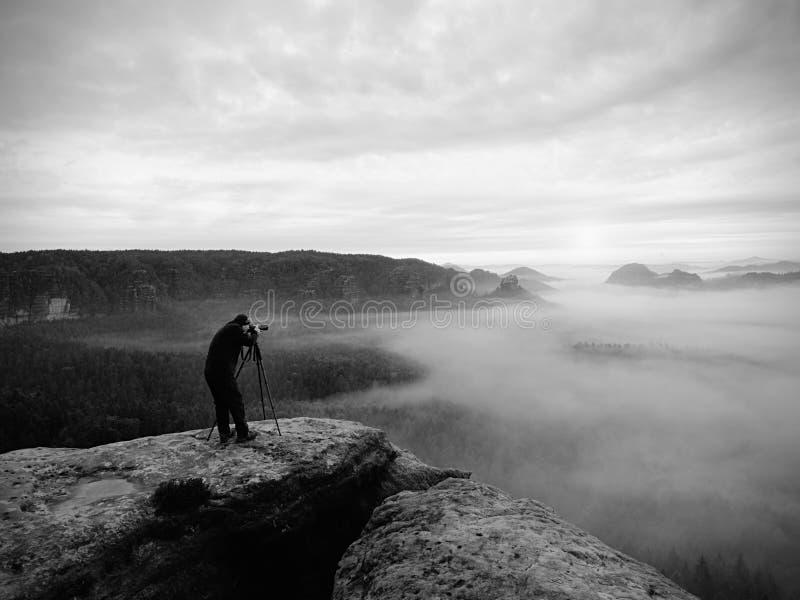 Artista de la foto en trabajo Fotógrafo en montañas El viajero toma las fotos del paisaje majestuoso, fotos de archivo libres de regalías