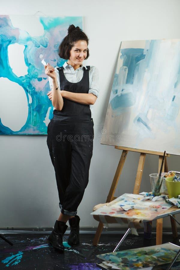 Artista de la muchacha en uniforme en el taller sobre el fondo de im?genes fotografía de archivo