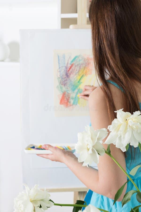 Artista de la muchacha que pinta una pintura abstracta con los pasteles de la tiza en el Libro Blanco fotografía de archivo