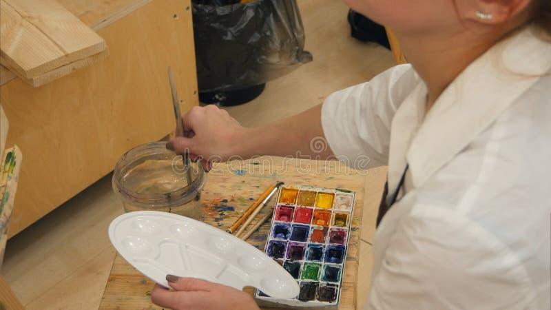 Artista de la mujer que prepara el cepillo y acuarelas para pintar foto de archivo