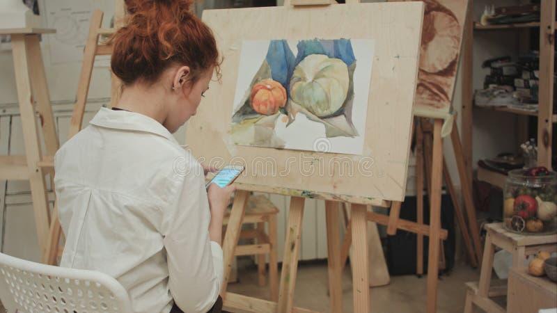 Artista de la mujer que se sienta delante de mensajería del caballete en el teléfono fotografía de archivo