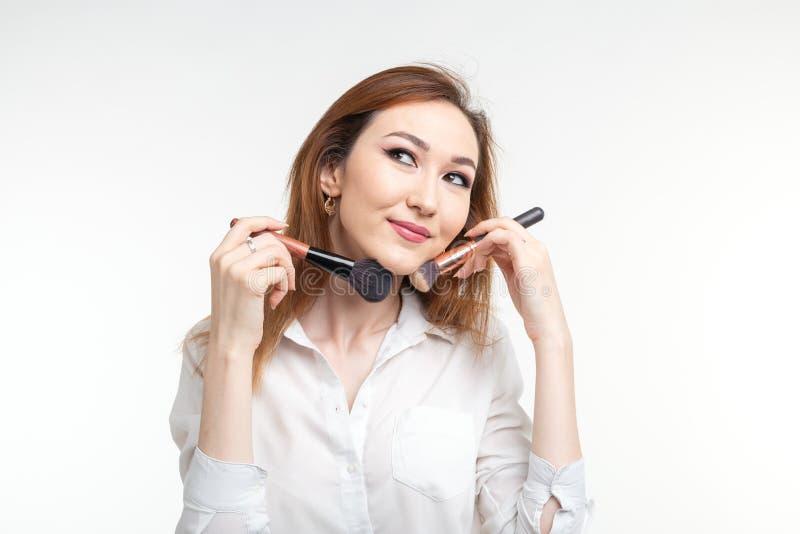 Artista de maquillaje, belleza y concepto de la gente - mujer joven coreana hermosa que sostiene cepillos del maquillaje en el fo fotografía de archivo libre de regalías