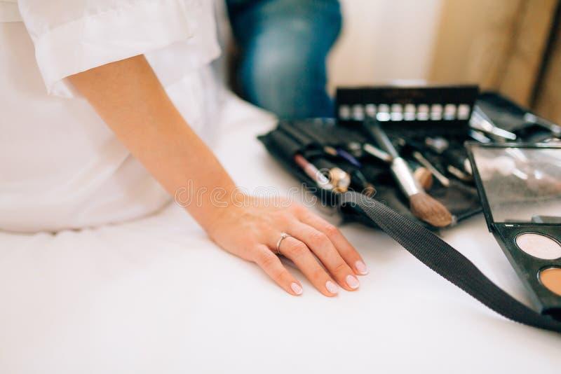 Artista de maquillaje de la boda que hace a una novia del compensar Atractivo hermoso fotografía de archivo libre de regalías
