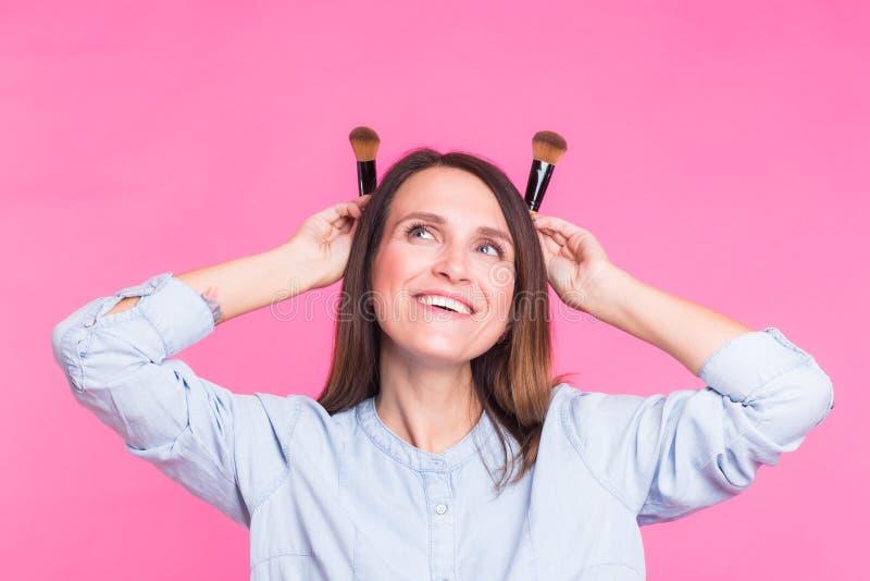 Artista de maquillaje divertido con los cepillos en fondo rosado fotografía de archivo