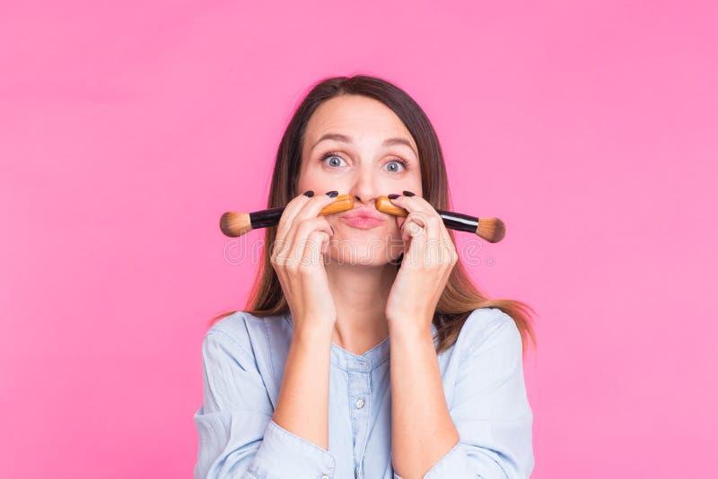 Artista de maquillaje divertido con los cepillos en fondo rosado foto de archivo libre de regalías