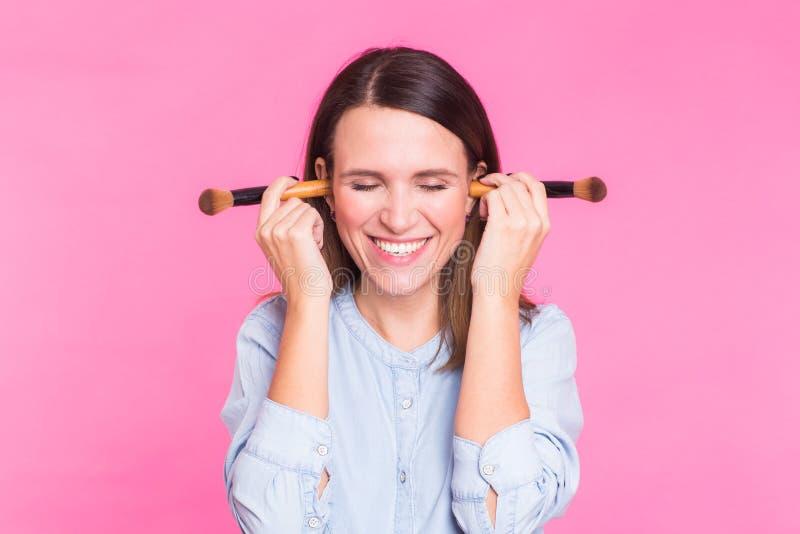 Artista de maquillaje divertido con los cepillos en fondo rosado imágenes de archivo libres de regalías