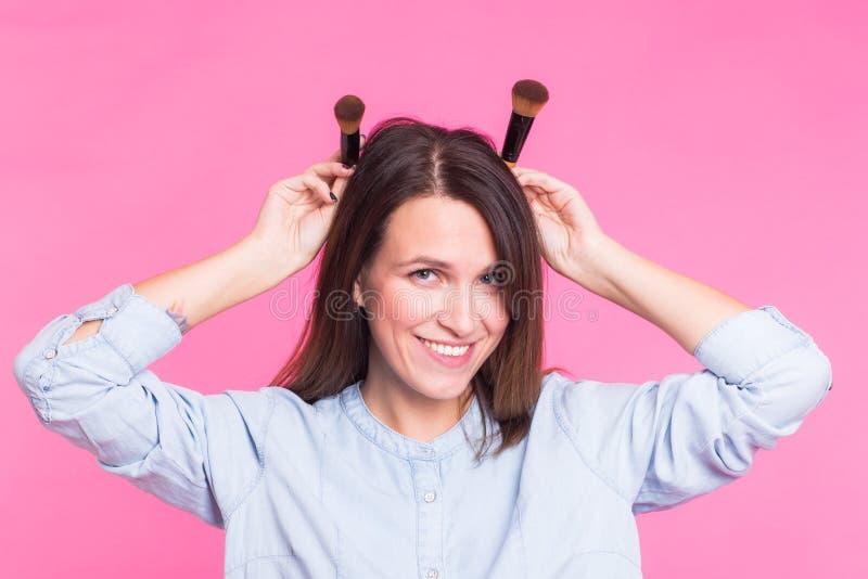 Artista de maquillaje divertido con los cepillos en fondo rosado fotos de archivo libres de regalías