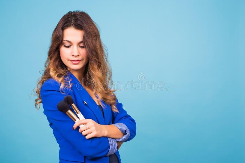 Artista de maquillaje joven con los cepillos en fondo azul imagenes de archivo