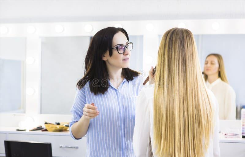 Artista de maquillaje joven que hace cambio de imagen al modelo bonito fotografía de archivo