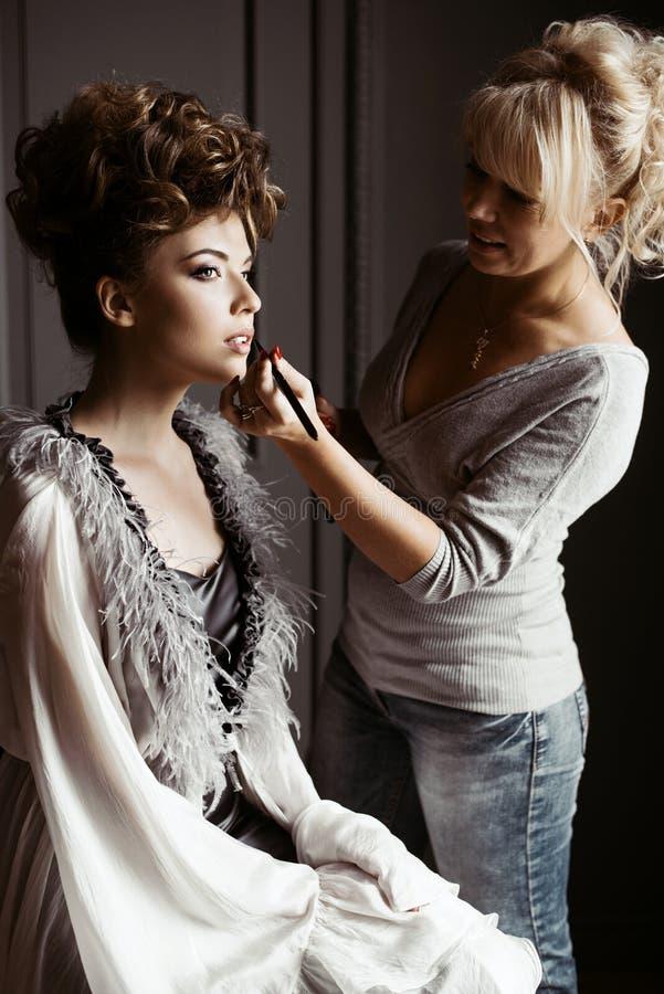 Artista de maquillaje de la boda que hace a una novia del compensar imagen de archivo libre de regalías