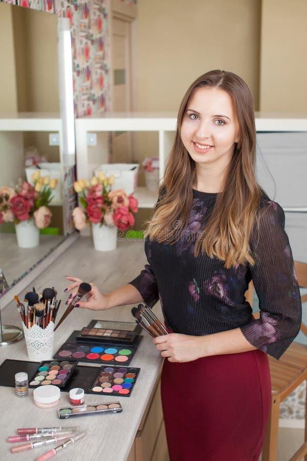 Artista de maquillaje lindo con los cepillos en las manos que miran la cámara aislada en estudio en el fondo blanco Componga al a foto de archivo