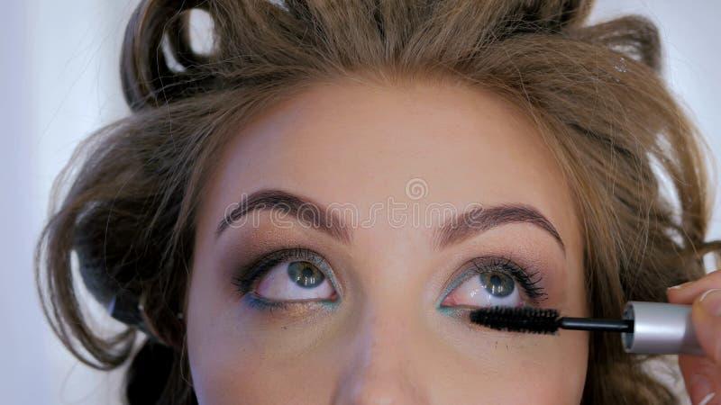 Artista de maquillaje profesional que aplica el rimel en las pestañas del modelo fotos de archivo libres de regalías