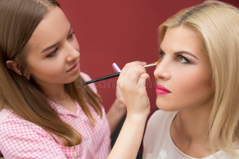Artista de maquillaje profesional que hace el modelo del encanto foto de archivo libre de regalías
