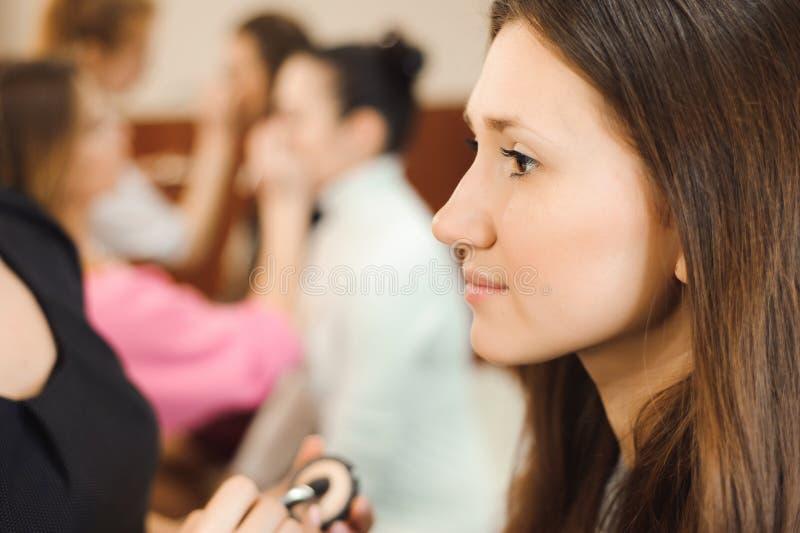 Artista de maquillaje profesional que trabaja con la mujer joven hermosa imagen de archivo libre de regalías