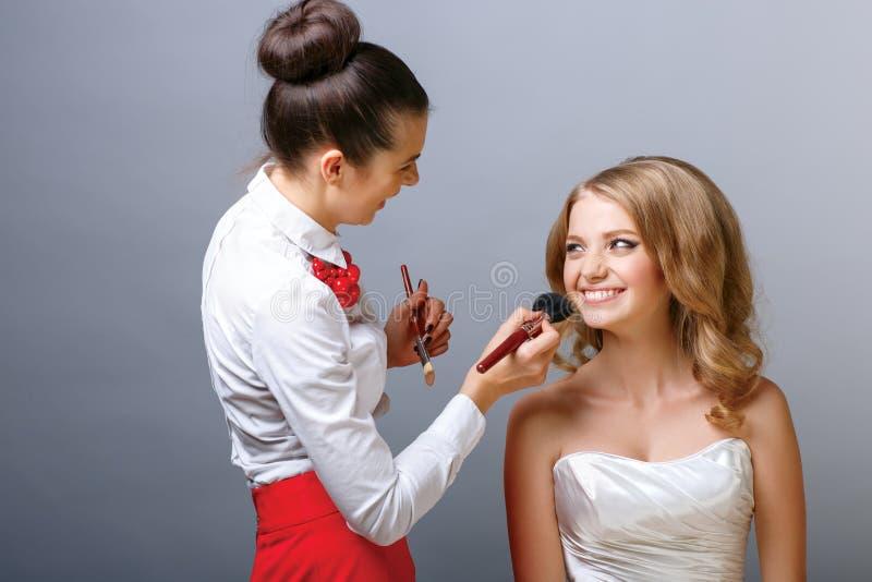 Artista de maquillaje que aplica el polvo con un cepillo en el modelo imagen de archivo