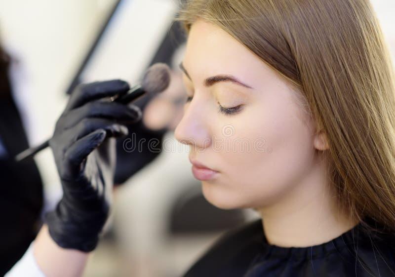 Artista de maquillaje que aplica el tono de la fundaci?n usando cepillo especial en modelo hermoso joven de la cara Cuidado facia fotografía de archivo