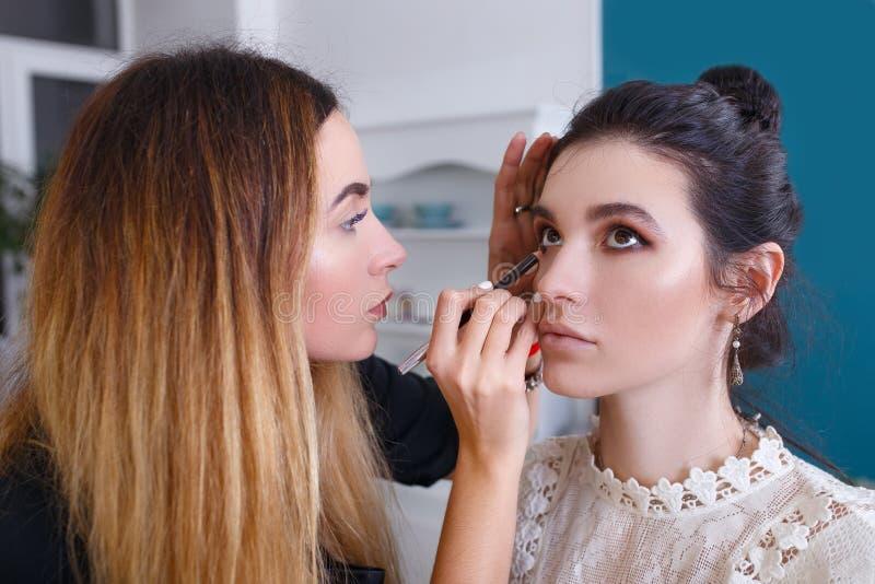 Artista de maquillaje que aplica lápiz de ojos imágenes de archivo libres de regalías