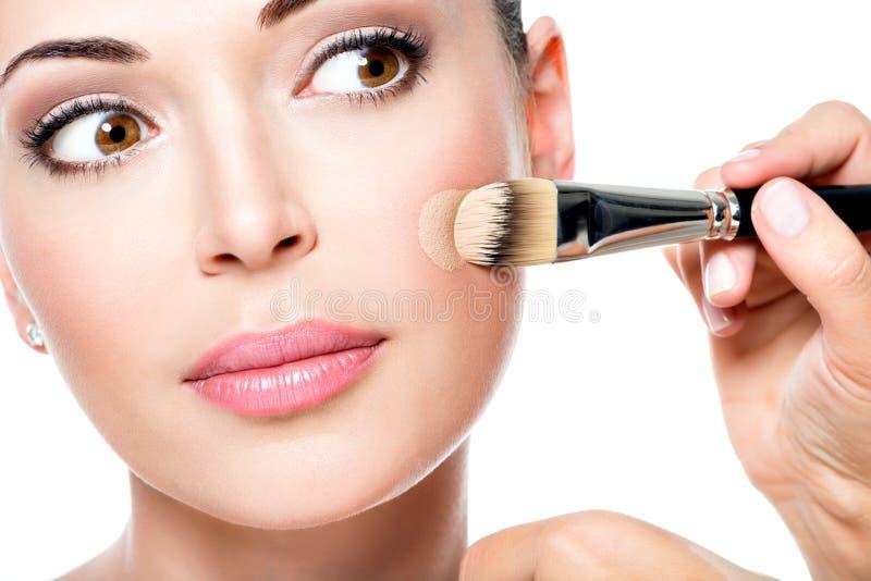 Artista de maquillaje que aplica la fundación tonal líquida en la cara fotos de archivo