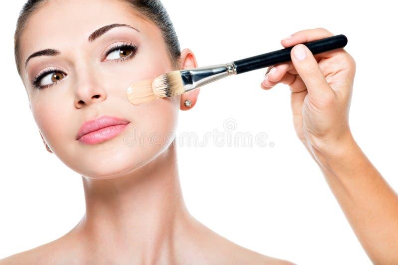 Artista de maquillaje que aplica la fundación tonal líquida en la cara imagen de archivo libre de regalías