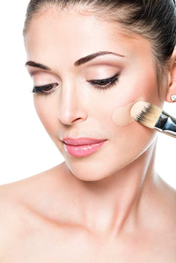 Artista de maquillaje que aplica la fundación tonal líquida en la cara foto de archivo libre de regalías