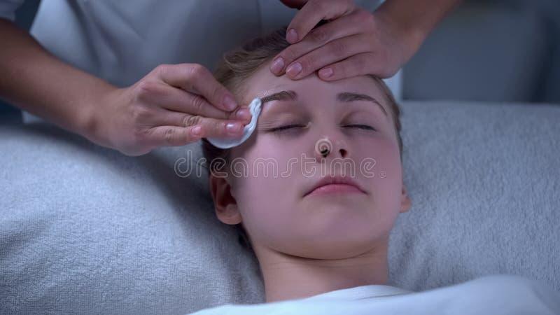 Artista de maquillaje que desinfecta las cejas después de la corrección y de la pintura, salón de belleza imagen de archivo libre de regalías