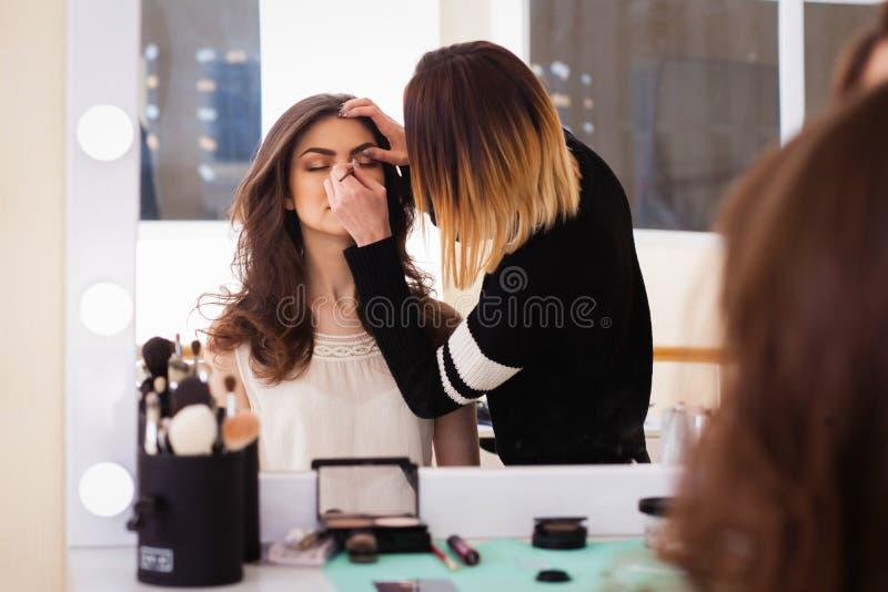 Artista de maquillaje que hace a la muchacha de maquillaje en el salón, concepto de la belleza fotografía de archivo libre de regalías