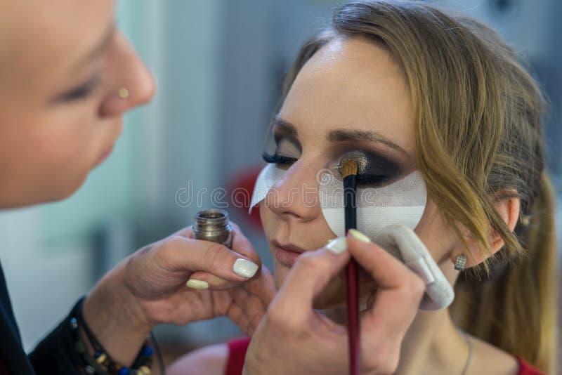 Artista de maquillaje que hace maquillaje ahumado de los ojos a la chica joven hermosa foto de archivo