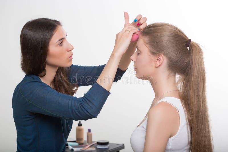 Artista de maquillaje que hace maquillaje de un joven hermoso imágenes de archivo libres de regalías