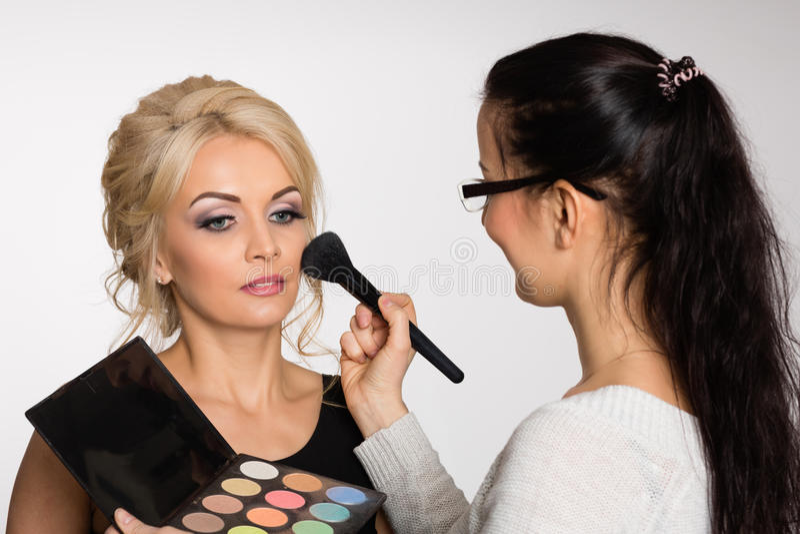 Artista de maquillaje que hace maquillaje de una chica joven hermosa foto de archivo libre de regalías