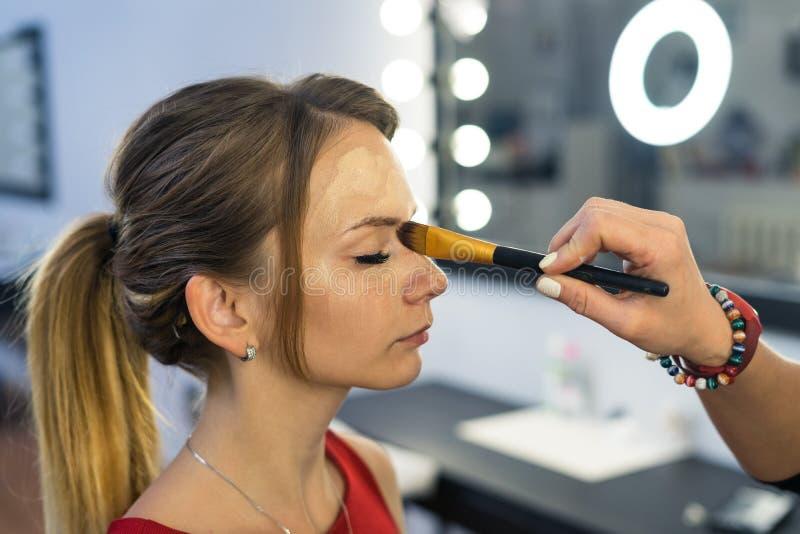 Artista de maquillaje que hace maquillaje a la chica joven hermosa imagen de archivo libre de regalías