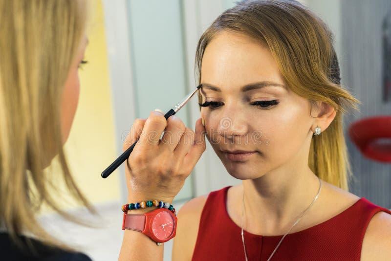 Artista de maquillaje que hace maquillaje a la chica joven hermosa foto de archivo