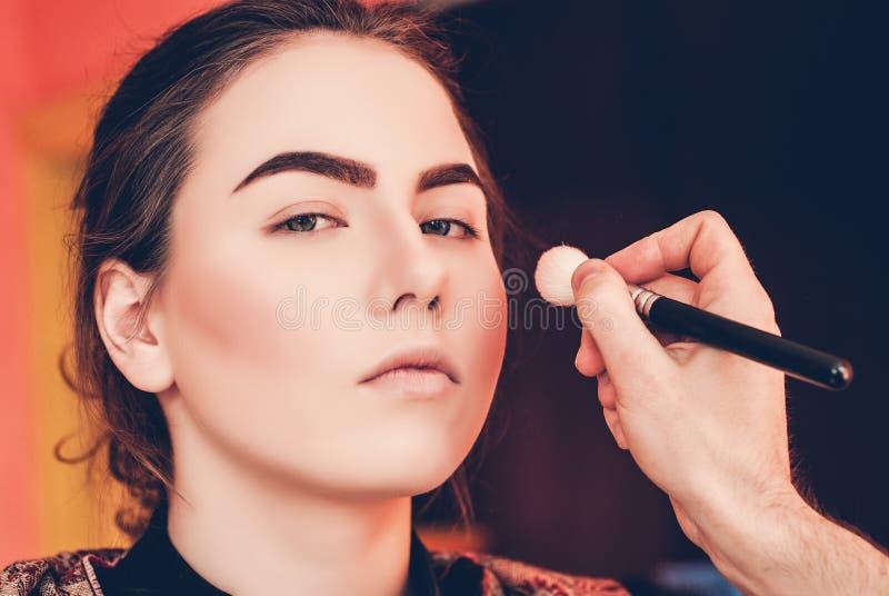 Artista de maquillaje que hace maquillaje de una chica joven hermosa en el estudio imagen de archivo