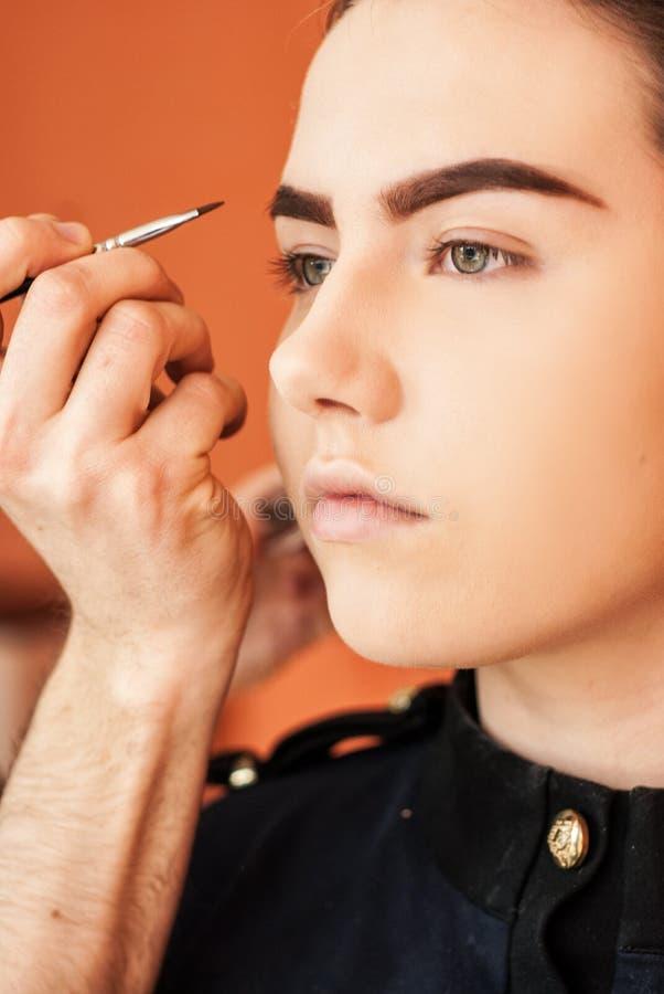 Artista de maquillaje que hace maquillaje de una chica joven hermosa en el estudio imagen de archivo libre de regalías