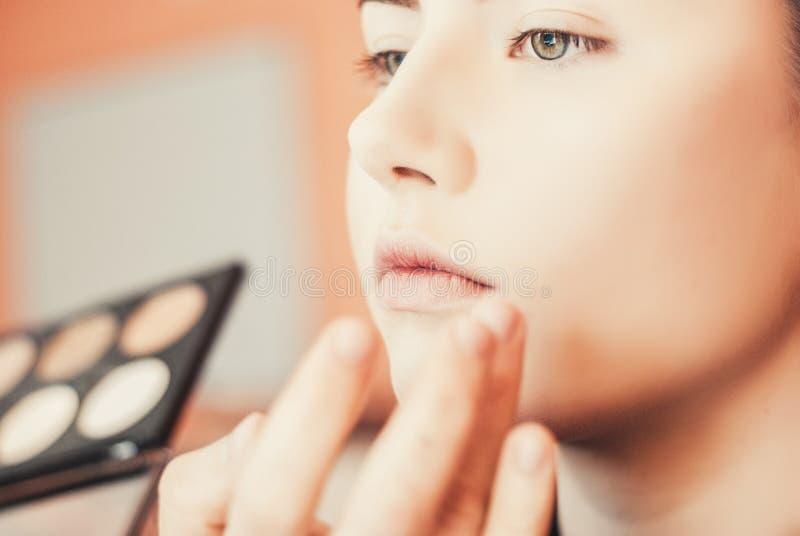 Artista de maquillaje que hace maquillaje de una chica joven hermosa en el estudio imágenes de archivo libres de regalías