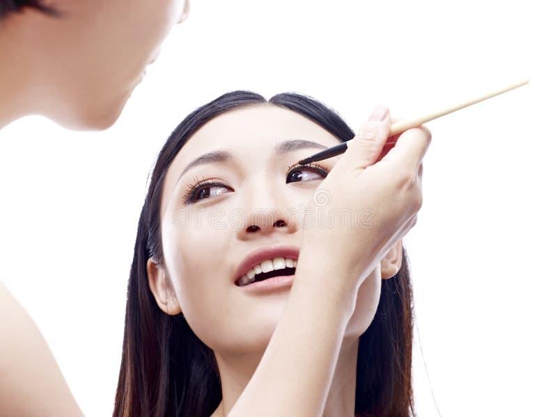 Artista de maquillaje que trabaja en un modelo asiático femenino imágenes de archivo libres de regalías