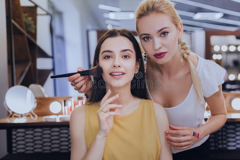 artista de maquillaje Rubio-cabelludo que mantiene a su cliente en salón de la belleza fotografía de archivo
