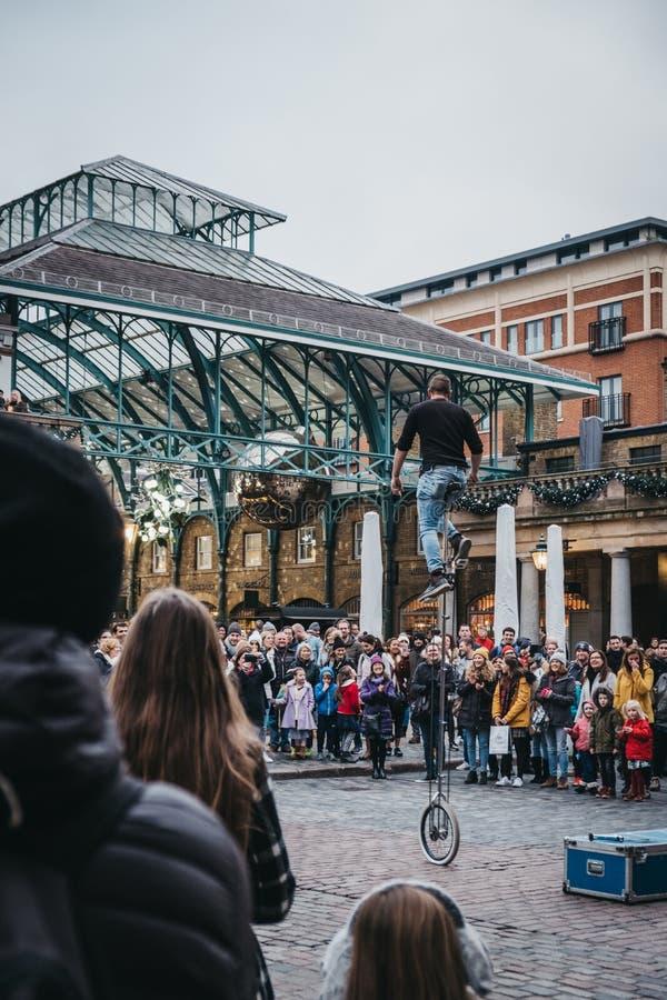 Artista de observación de la calle de la muchedumbre que se realiza delante del mercado de Covent Garden, Londres, Reino Unido foto de archivo