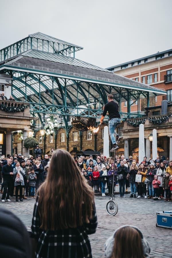 Artista de observación de la calle de la muchedumbre que se realiza delante del mercado de Covent Garden, Londres, Reino Unido imagen de archivo