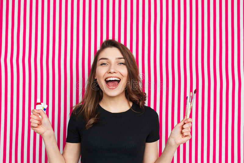 Artista de sexo femenino alegre con las brochas fotografía de archivo libre de regalías